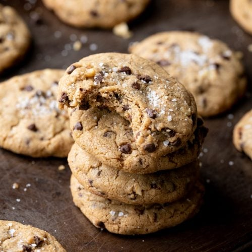 stacked chocolate chip cookies on a baking sheet