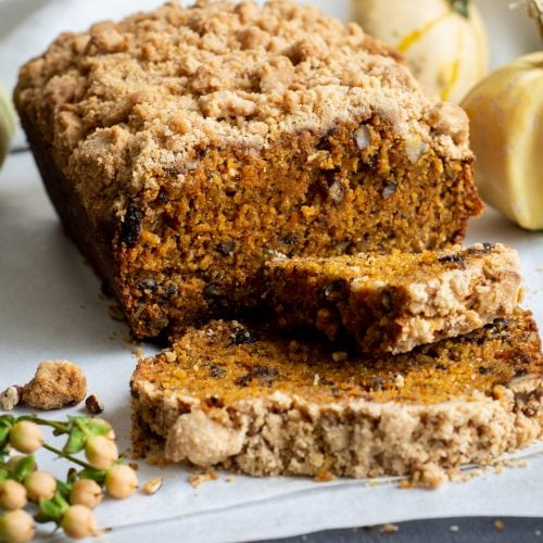 loaf of spiced carrot crumb cake with two slices and crumbs on table