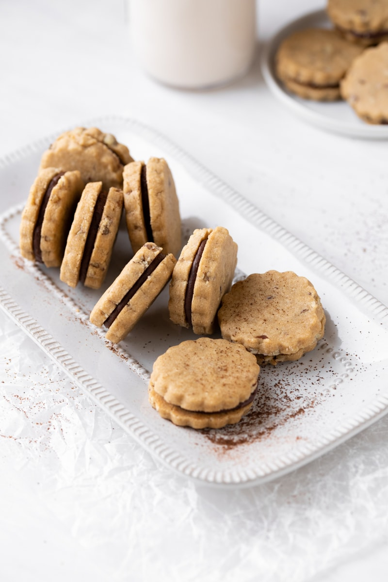 espresso sandwich cookies on a white place with a jar of milk