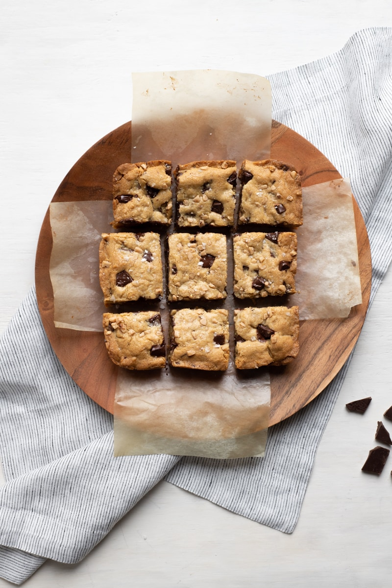 overhead photo of blondies on a wood round plate
