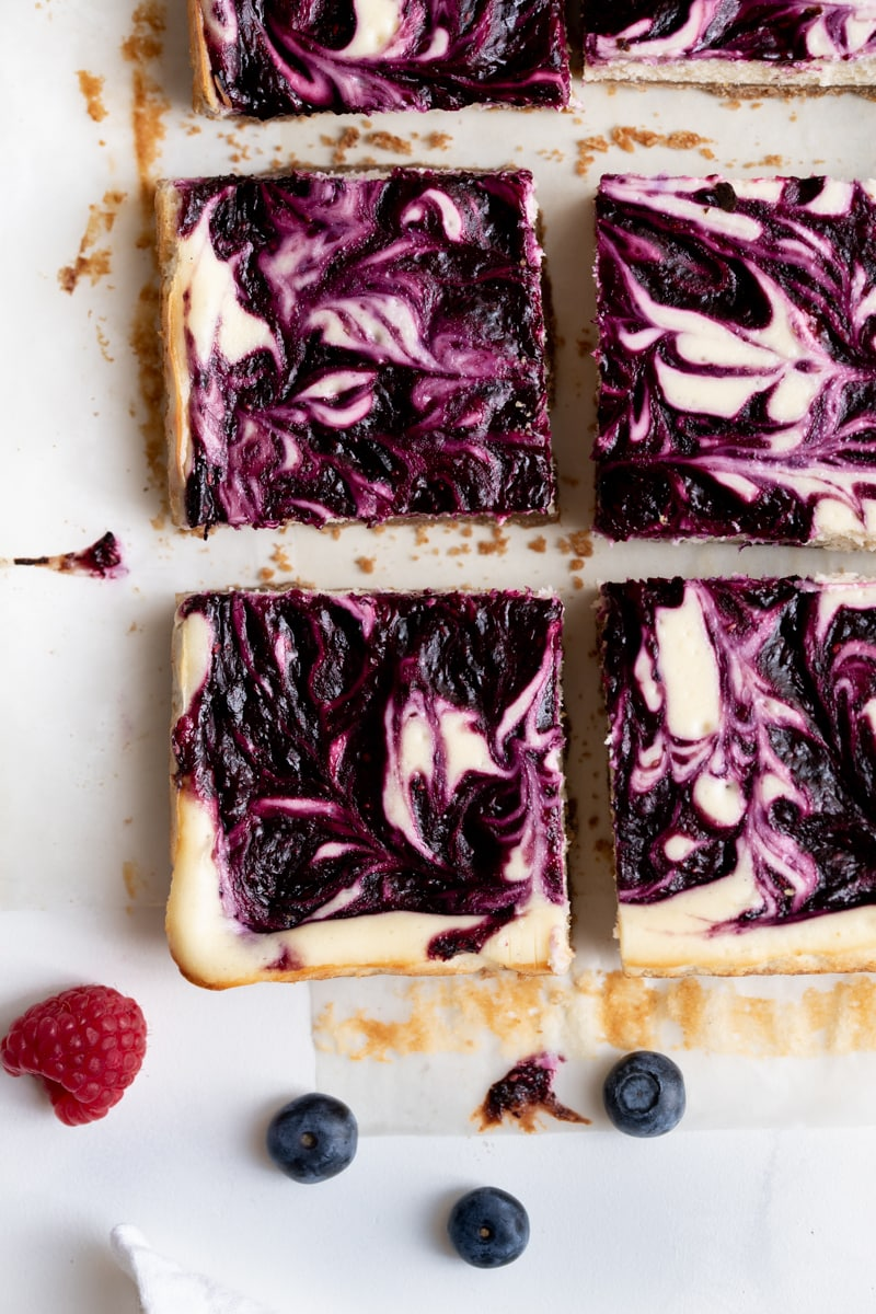 Overhead photo of mixed berry cheesecake squares on a white table.
