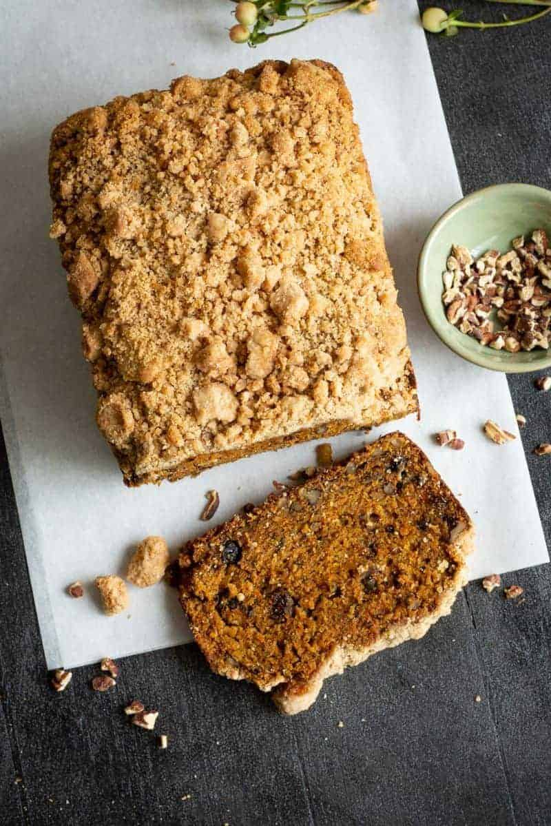 overhead photo of spiced carrot crumb cake loaf with slice and bowl of walnuts